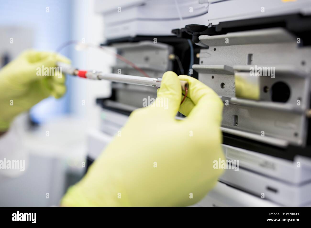Glass column containing a solution for calibrating a mass spectrometer. Mass spectrometry uses strong magnetic and electric fields to separate the components of a sample by mass and charge. This enables researchers to determine the elemental composition of the sample. Stock Photo