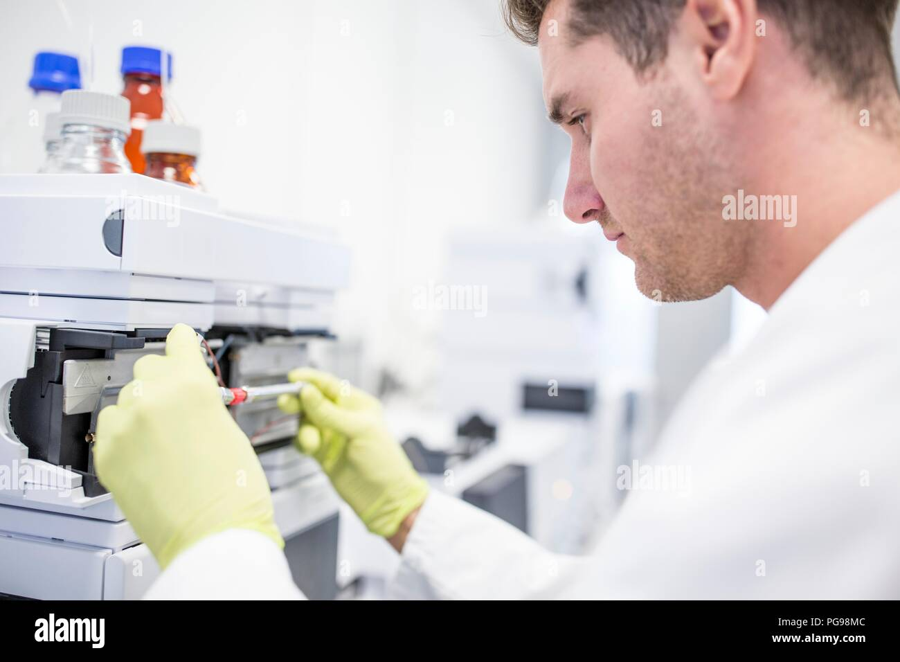 Technician placing a glass column containing a calibration solution in to a mass spectrometer. Mass spectrometry uses strong magnetic and electric fields to separate the components of a sample by mass and charge. This enables researchers to determine the elemental composition of the sample. - Stock Image