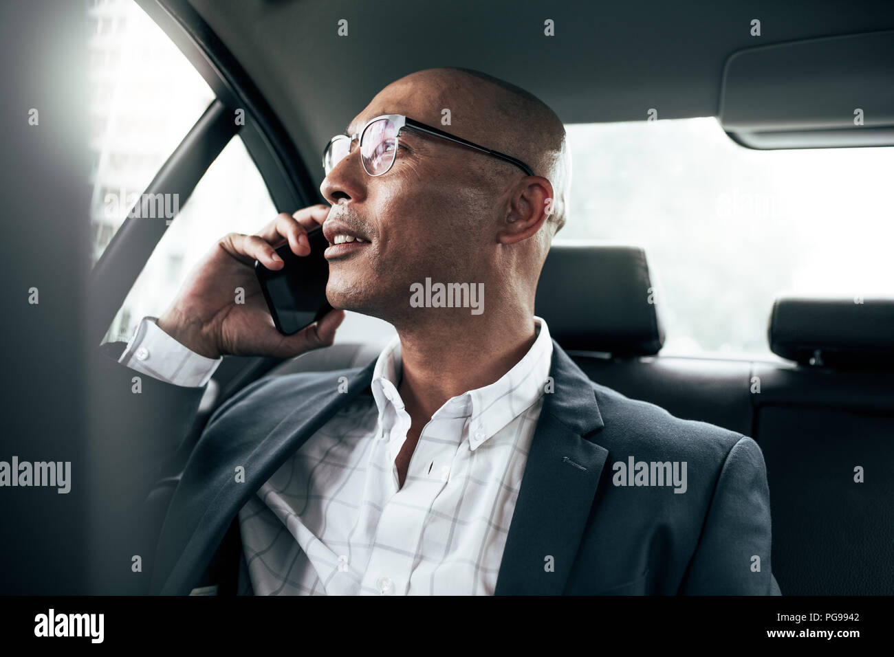 Businessman wearing eyeglasses talking over cell phone sitting in his sedan looking out the window. Man managing business on mobile phone sitting in c - Stock Image