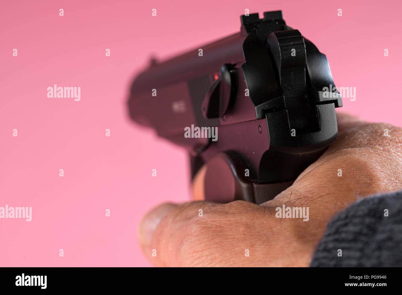 Male hand aiming gun. - Stock Image