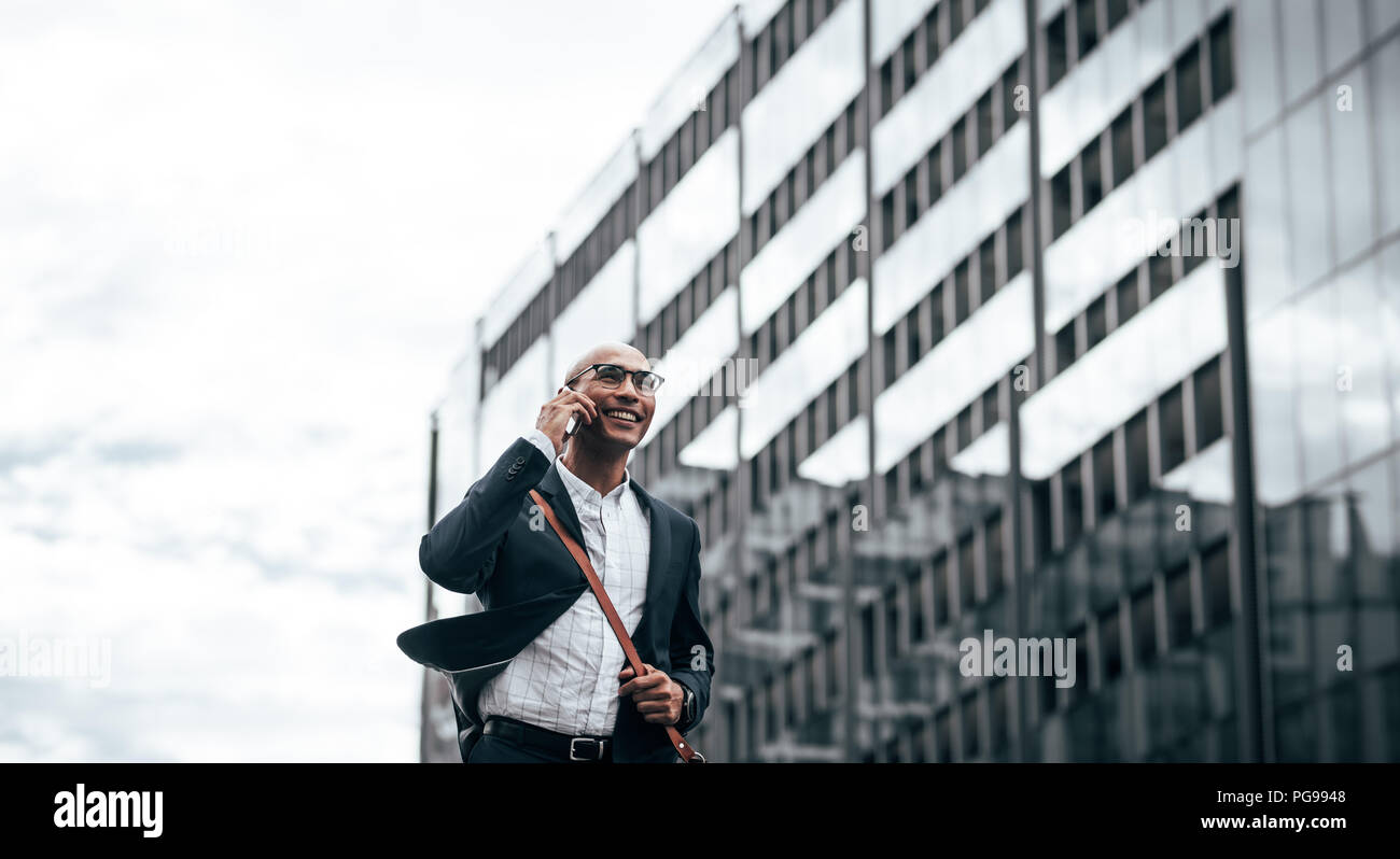 Smiling businessman talking over cell phone while commuting to office with a glass facade building in background. Man in formal clothes carrying offic - Stock Image