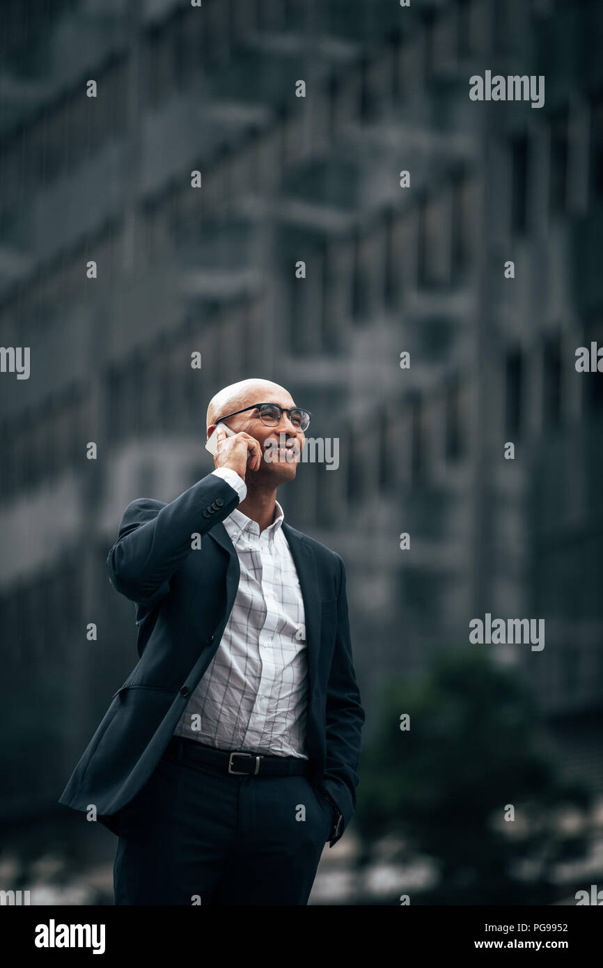 Smiling businessman talking over cell phone standing outdoors with a hand in pocket. Man in formal clothes walking on street talking on mobile phone w - Stock Image