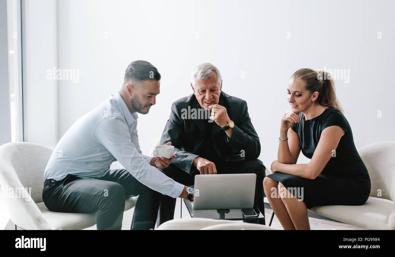 Male executive viewing proposal on laptop to his colleagues in office foyer. Group of three business professionals working together on new business pl - Stock Image