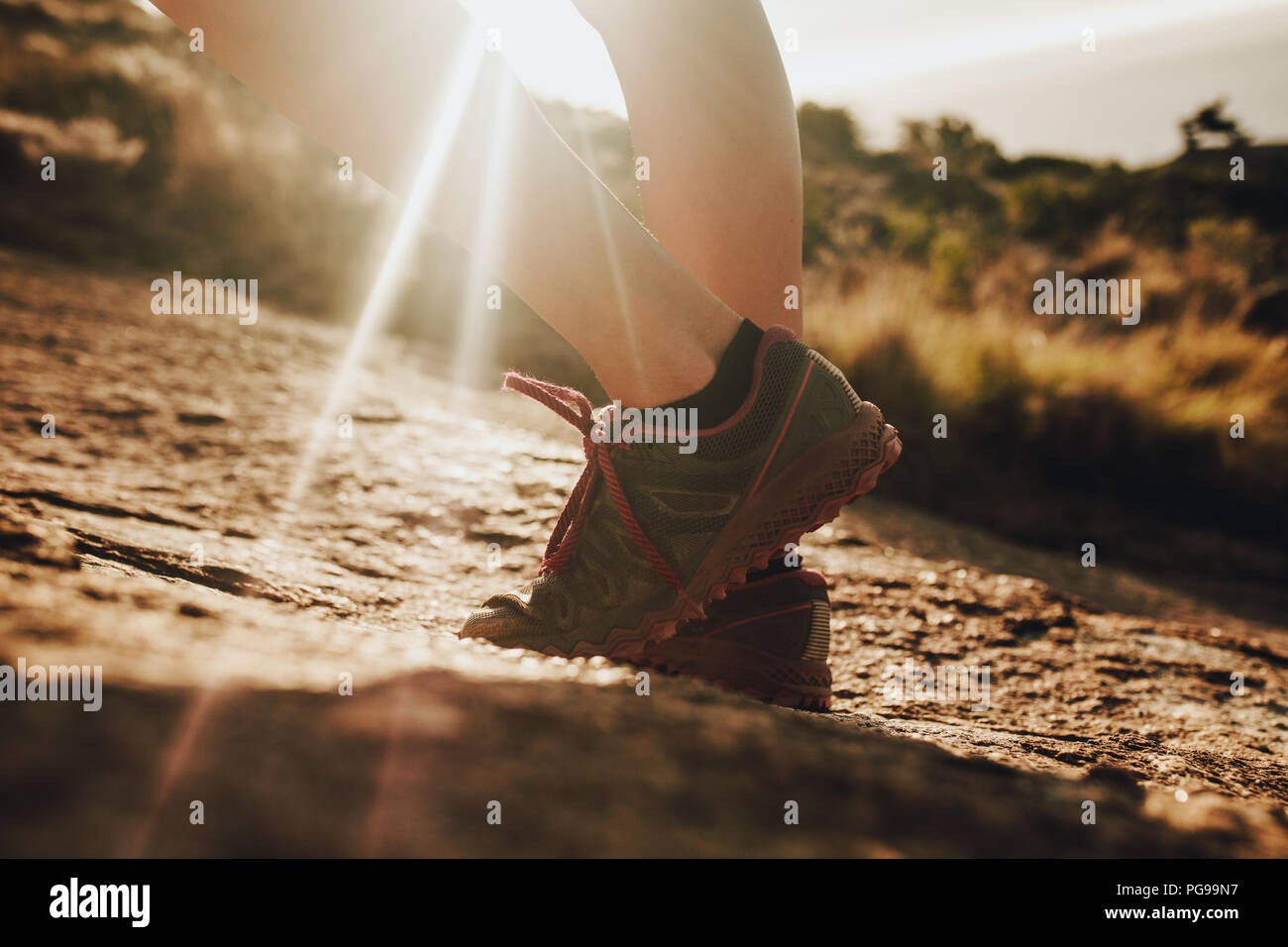 Close up female mountain trail runner wearing sports shoe standing in sunlight. Woman in running shoes standing in rocky trail. - Stock Image
