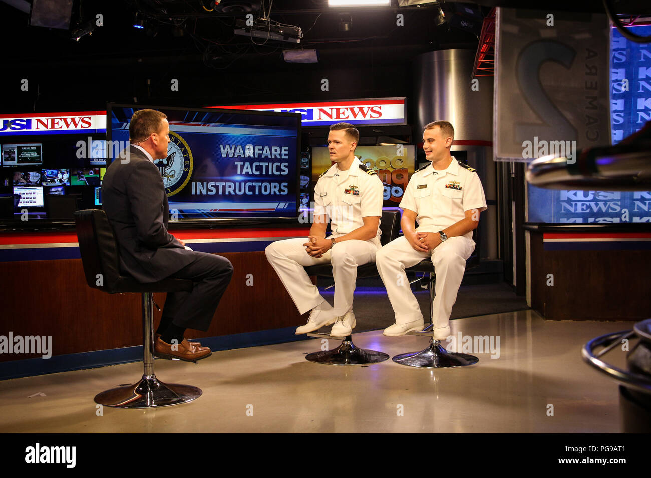 SAN DIEGO (Aug. 18, 2018) Lt. Matt Clark, center, and Lt. Caleb Bekemeier, right, Warfare Tactics Instructors (WTI) from Naval Surface and Mine Warfighting Development Center (SMWDC) sit for an interview with broadcaster Jason Austell on KUSI's Good Morning San Diego. Clark and Bekemeier discussed the WTI program, its impact on Surface Fleet lethality and tactical proficiency, and WTI participation at the upcoming Surface Navy Association West Coast Symposium. Officers interested in the WTI program should contact SWO_WTI@Navy.mil for more information and to begin the application process. SMWDC - Stock Image