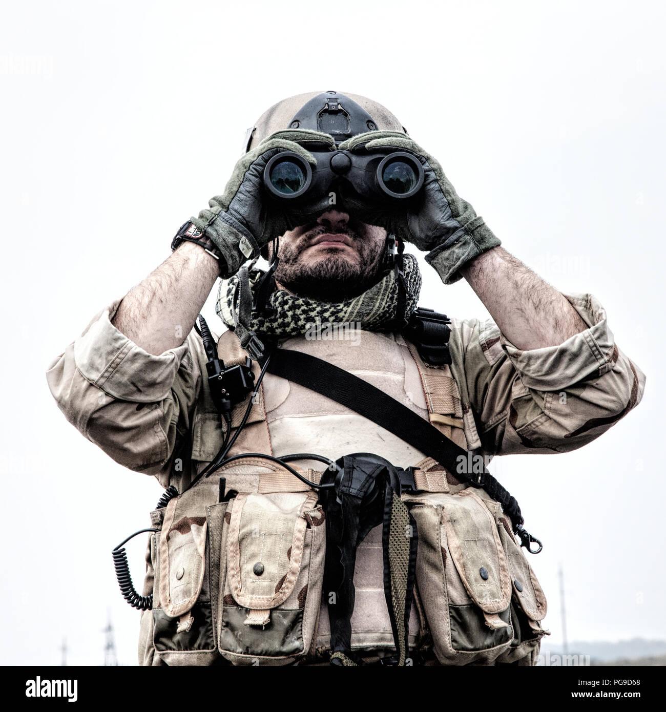 Commando soldier using binoculars to observe terrain - Stock Image