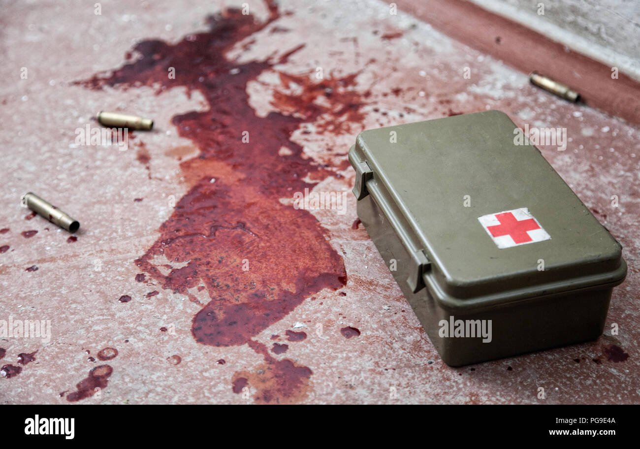 Military firs aid kit on floor with blood stains - Stock Image