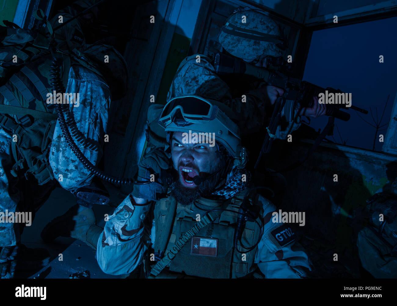 Army team leader coordinating teammates with radio - Stock Image