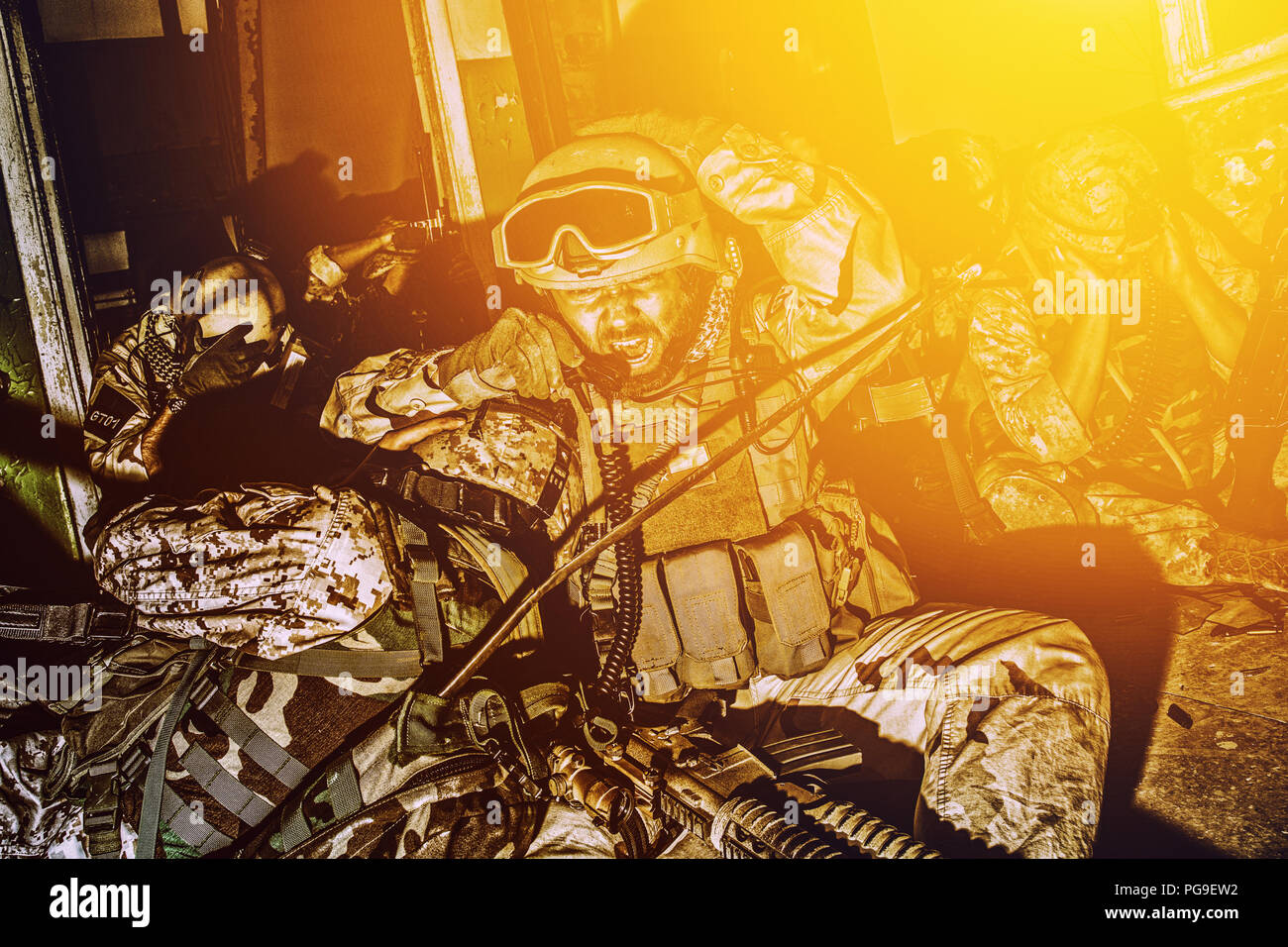 Army team leader coordinating teammates with radio Stock Photo