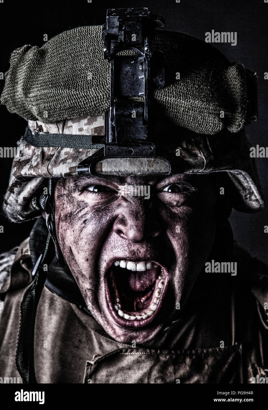 Mad army soldier screaming while looking at camera - Stock Image