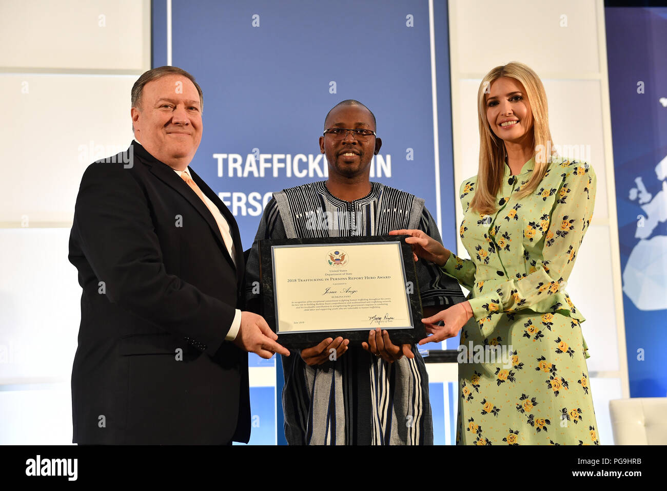 U.S. Secretary of State Mike Pompeo, joined by Advisor to the President Ivanka Trump, presents a certificate to 2018 'TIP Report Hero' Josue Ango of Burkina Faso. Ango is one of ten individuals from around the world who was recognized for his efforts to fight against human trafficking, at the U.S. Department of State on June 28, 2018. - Stock Image