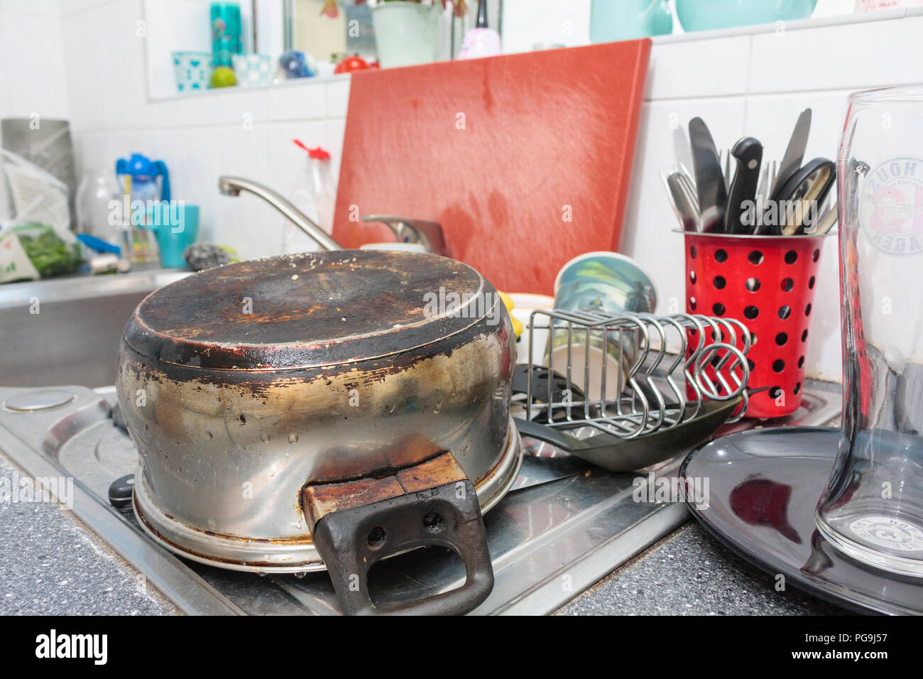A pile of clean kitchen utensils on the draining board of a kitchen sink - Stock Image