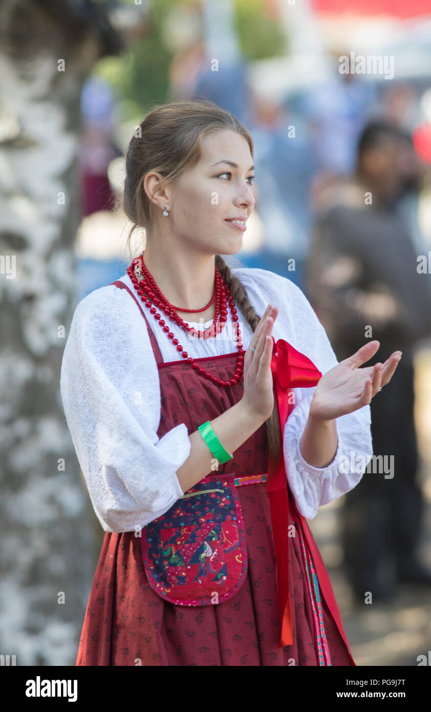 Beautiful Russian girl in a folk sundress claps her hands at a Slavic holiday Stock Photo