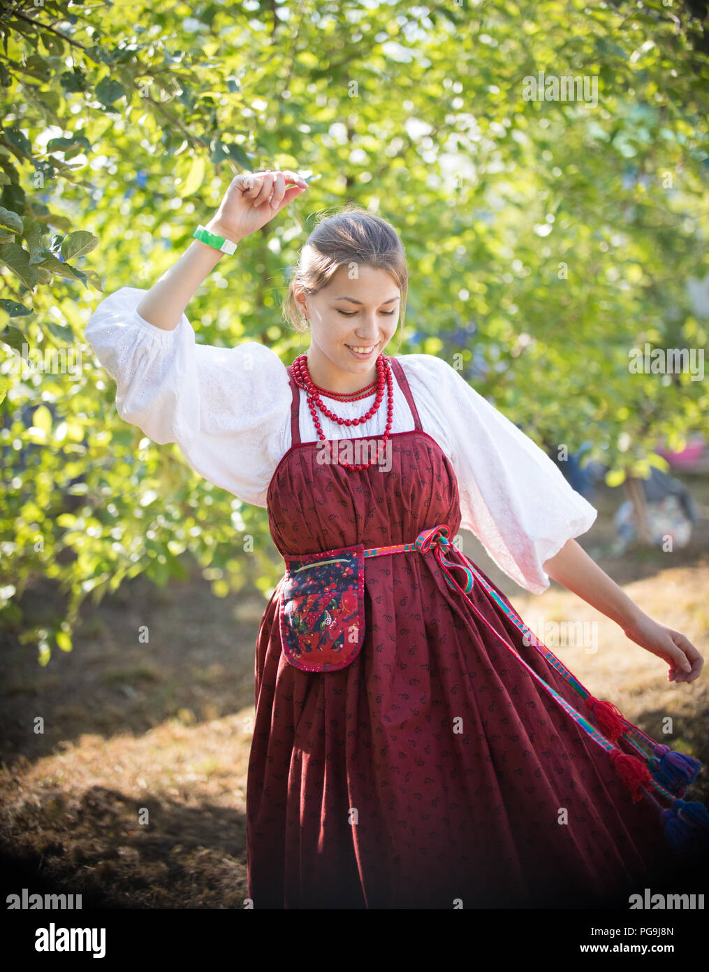 Beautiful young girl in Russian folk sundress dancing on the background of green trees - Stock Image