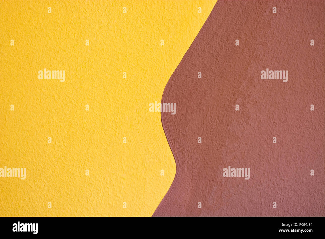 A fragment of a wall plastered in two colors, yellow and brown, for use as a background. - Stock Image