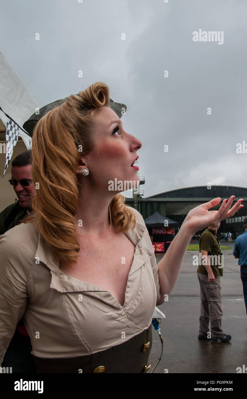 Female singer with American girl group Manhattan Dolls checking the British weather before an outdoor performance at Duxford airshow. Rain clouds - Stock Image