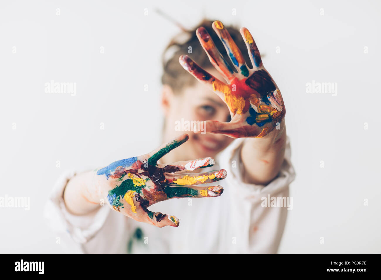 Happy woman hiding the face with her painted hands. Creative, art, childhood, drawing concept - Stock Image