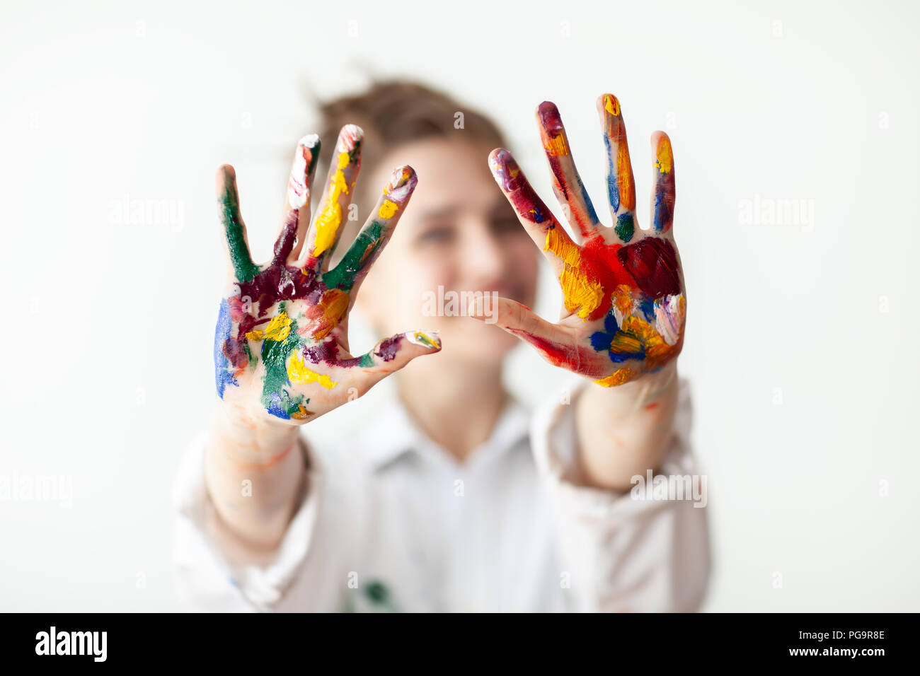 Happy woman showing hands painted in colorful paints on white background. Fun concept - Stock Image