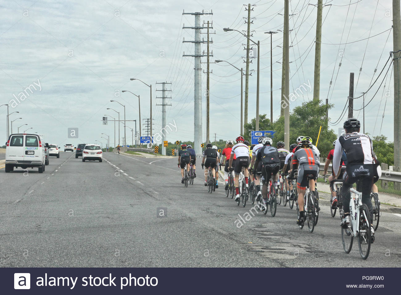 A group of bicyclists travel along a busy road in Toronto, Ontario, Canada. - Stock Image