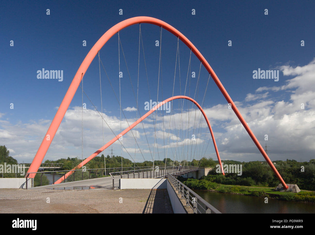 A modern suspension bridge for pedestrians over a canal in Gelsenkirchen, Germany. - Stock Image