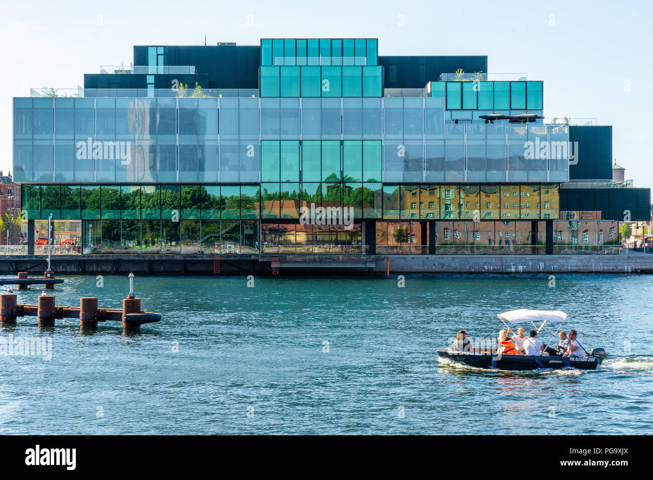 The Blox building from 2018 by the Copenhagen waterfront, domicile for DAC, Dansk Arkitektur Center. Leisure boat in front. - Stock Image
