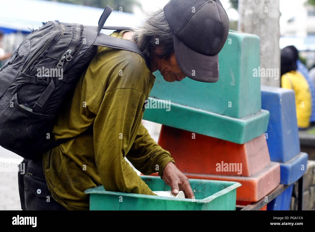Antipolo City, Philippines - August 18, 2018: A scavenger goes through trash bins to look for recyclable materials. - Stock Image