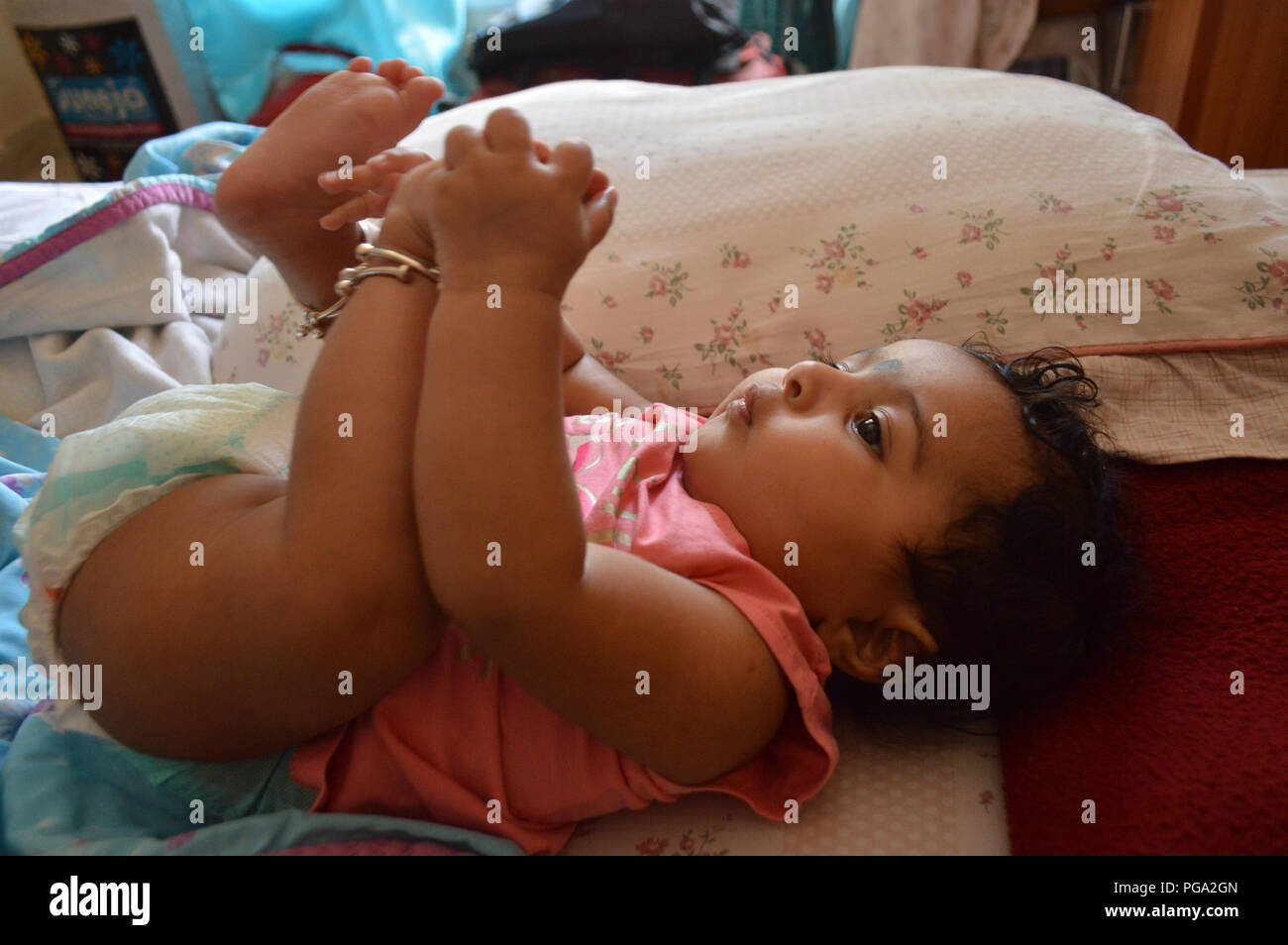 Infant in pink shirt lying on bed and holding her left foot and looking at it - Stock Image