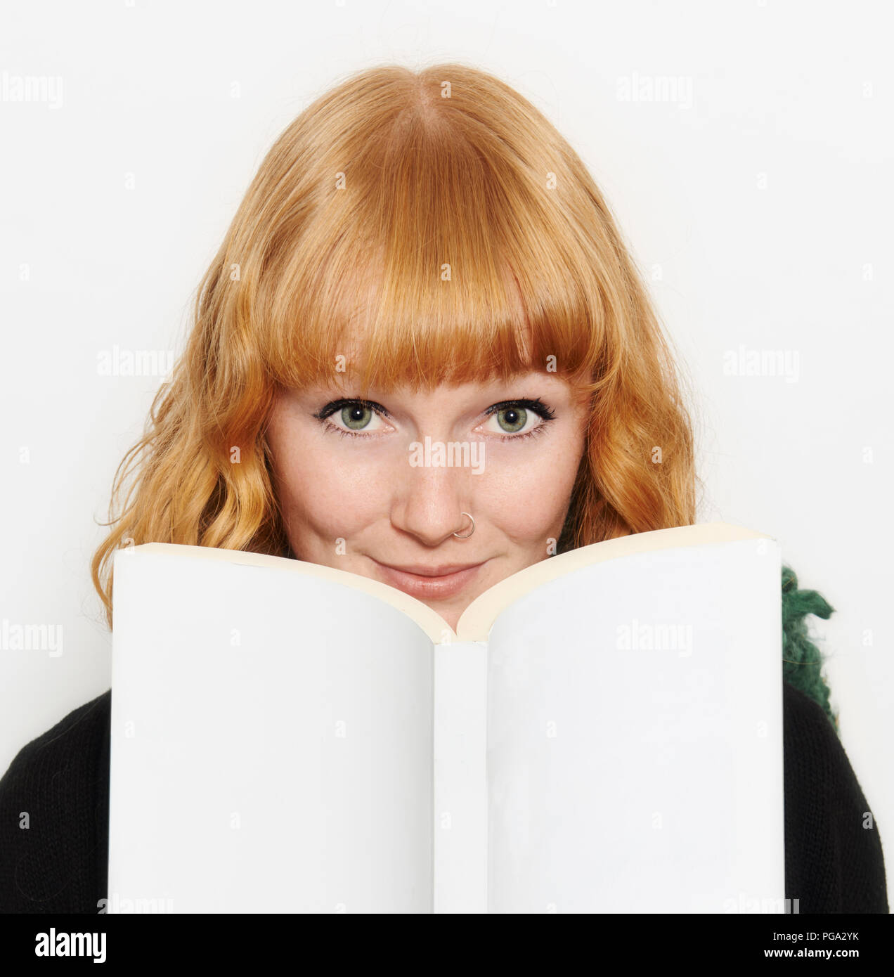 A red haired blue eyed girl looks up from reading her book. - Stock Image