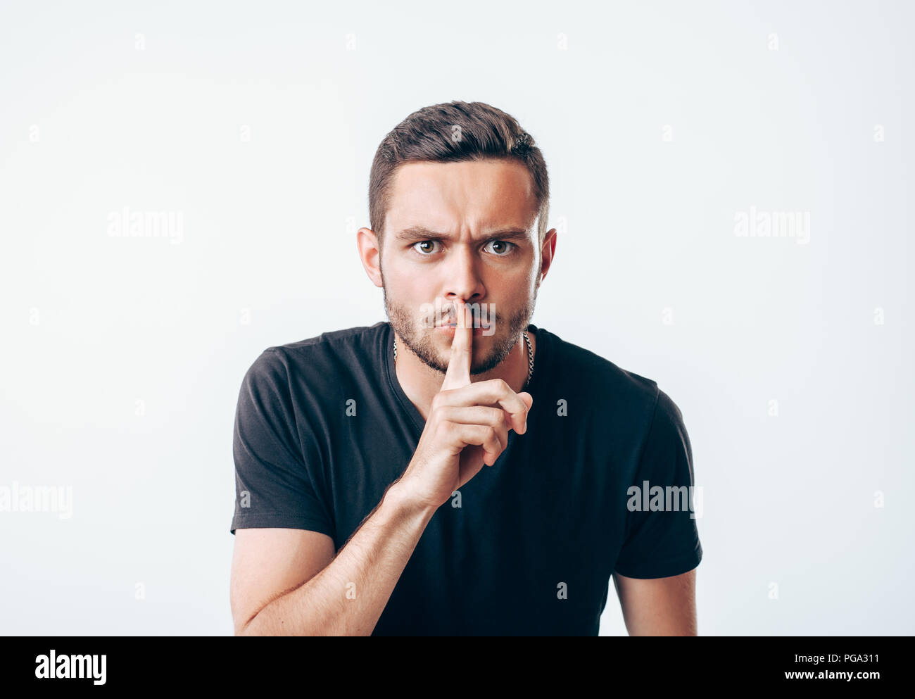 Young man holding index finger on lips asking for silence.  Secret concept - Stock Image
