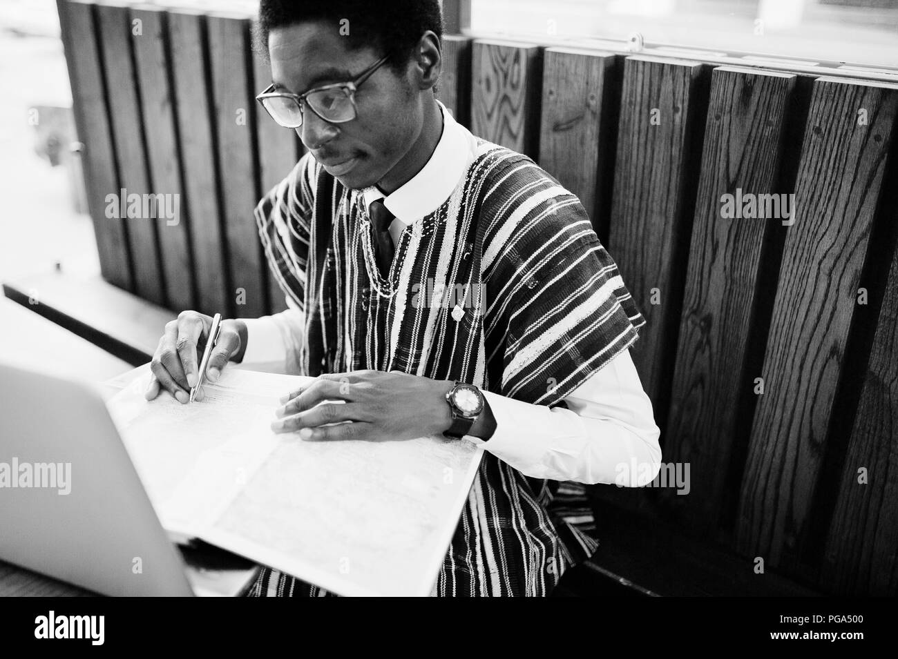 African man in traditional clothes and glasses sitting behind laptop at outdoor caffe and looking on map of Africa and Ghana at his notebook. - Stock Image