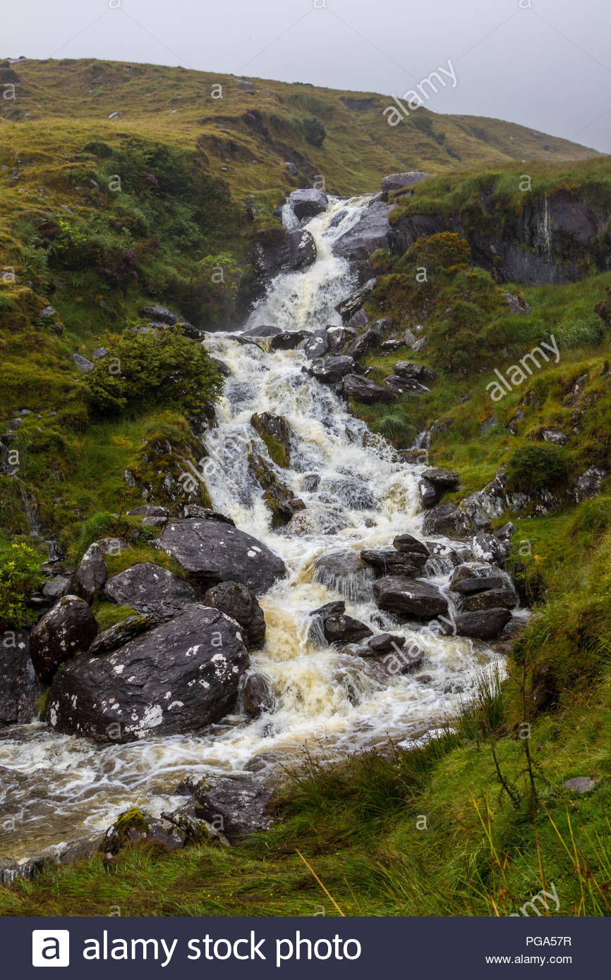 A mountain stream tumbles down a waterfall on the R574, Healy Pass, Beara, Republic of Ireland - Stock Image