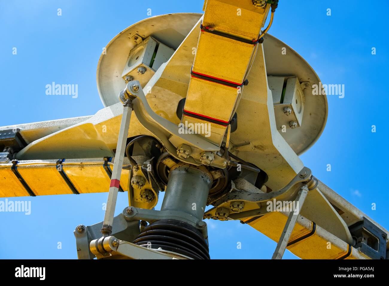 Close up of the rotors blades of a yellow Helicopter against a bright blue sky - Stock Image