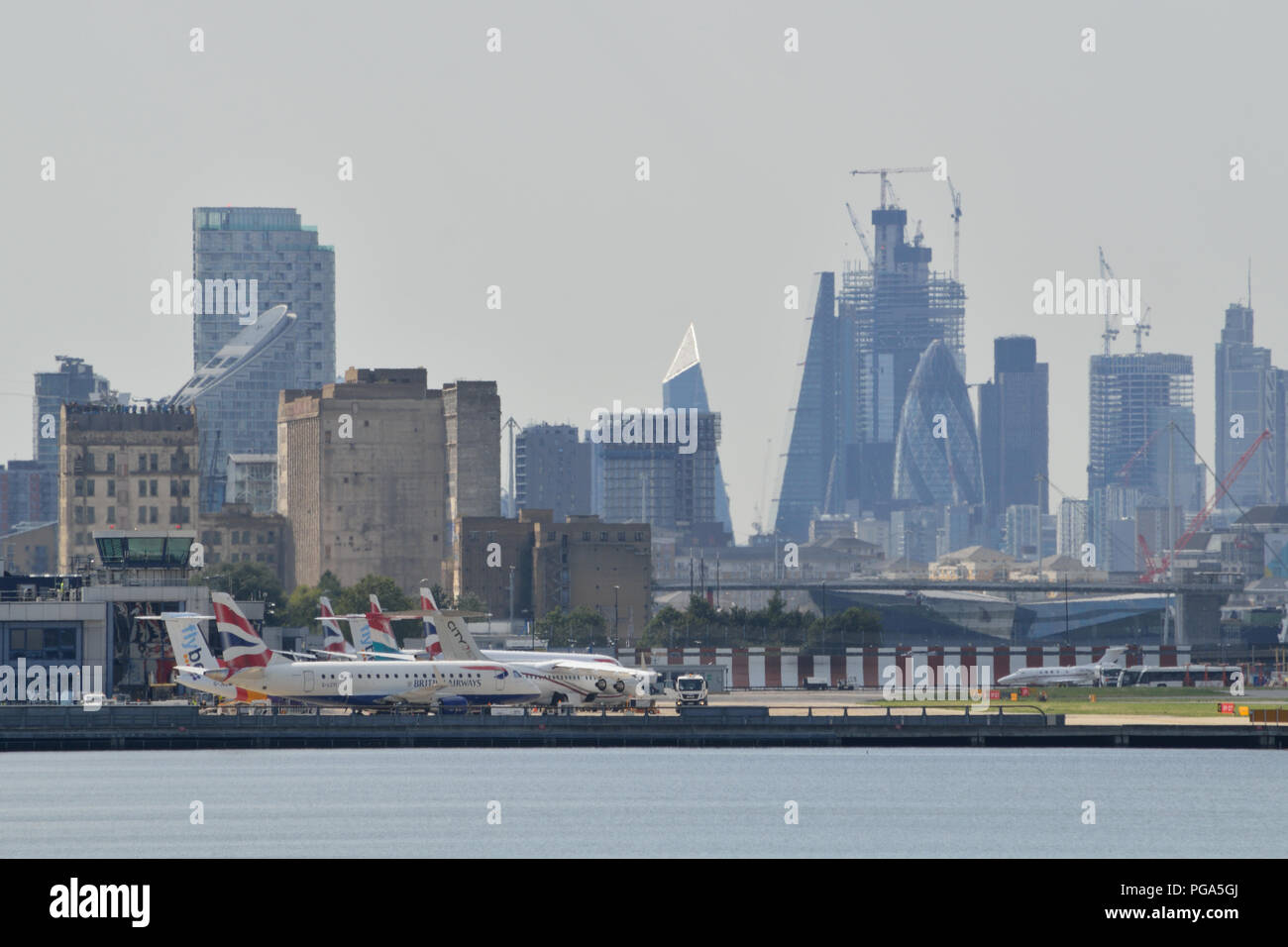 Planes wait on the apron at London City Airport with the City of London skyline in the background - Stock Image