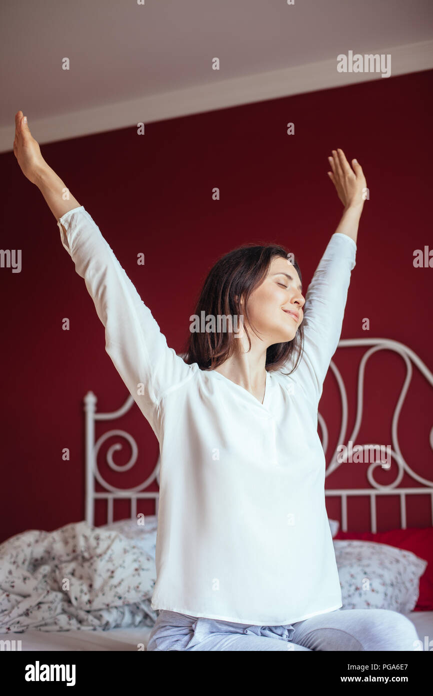 portrait of pretty woman stretching in bed after wake up good morning concept