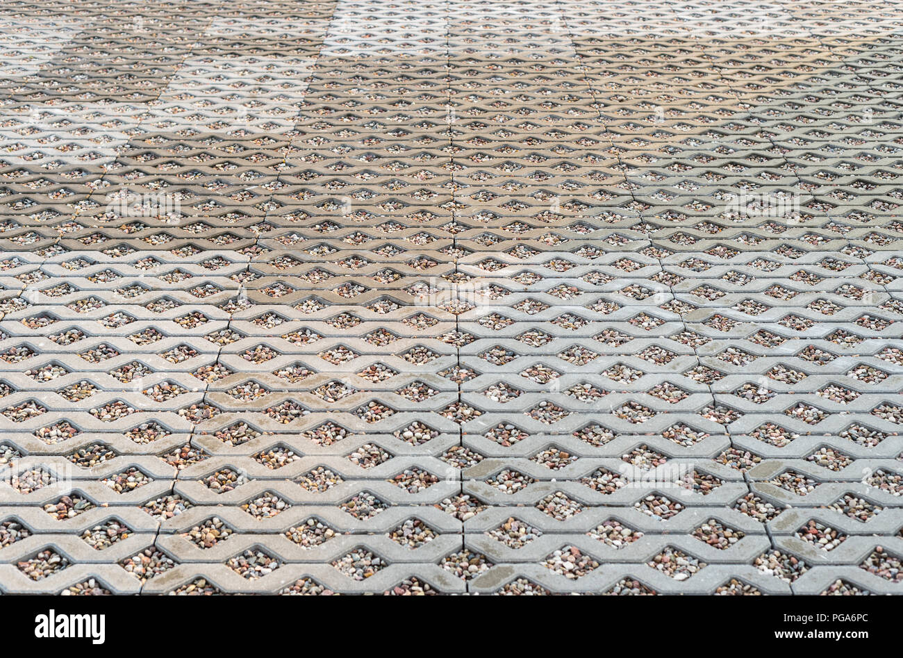 Wet openwork concrete pavement filled with colorful pebbles. - Stock Image