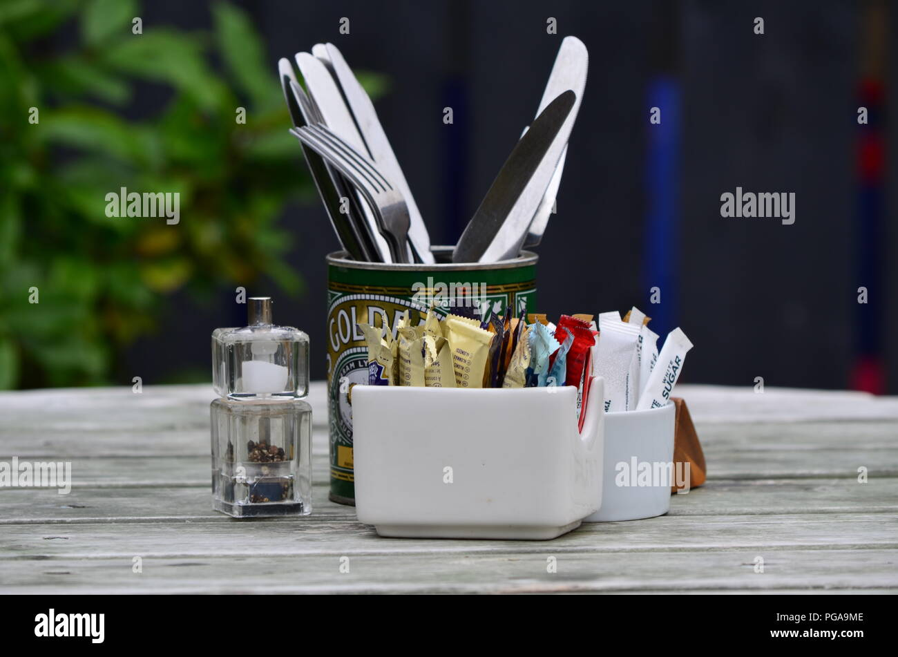 Collection of condiments, cutlery on sun-bleached picnic table - Stock Image