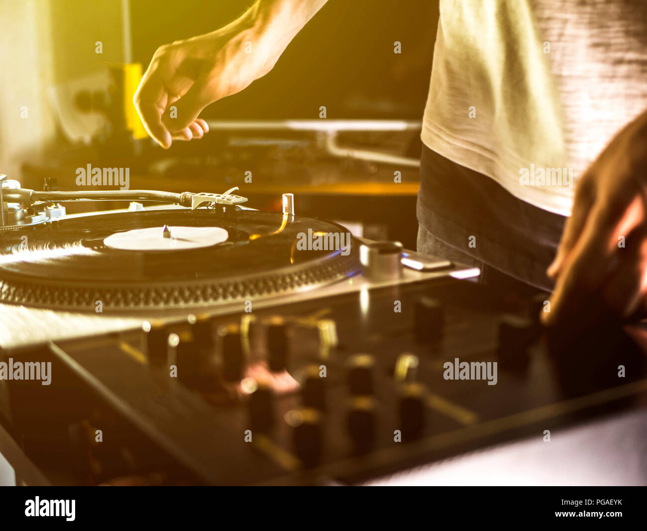 close up dj hand play music on turntable record setup at