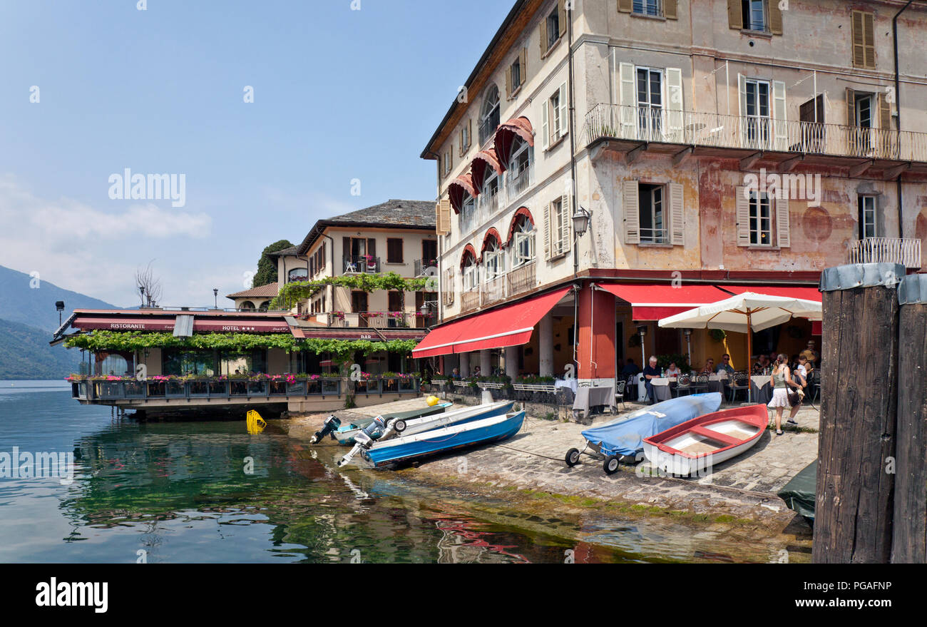 Portion of the lakefront with Ristorante Venus fronted by locals' boats pulled up on the shingle beach of Orta San Giulio, considered one of the most  - Stock Image