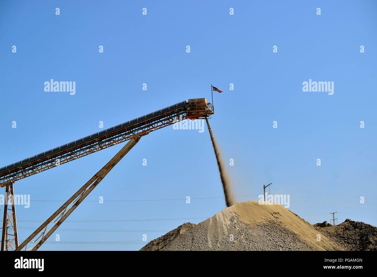 South Elgin, Illinois, USA. A conveyor belt delivers stone and gravel to form a large pile of material at a ready mix concrete plant. - Stock Image