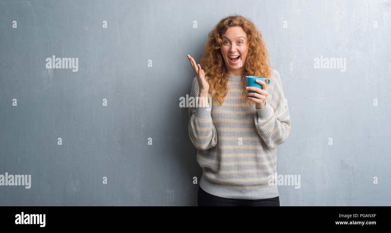 83ff1382fde Young redhead woman over grey grunge wall drinking a cup of coffee very  happy and excited, winner expression celebrating victory screaming with big  sm