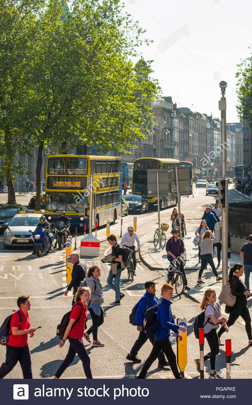 Pedestrians, bicyclist and automobile traffic on College Green, Dublin, Leinster, Ireland - Stock Image