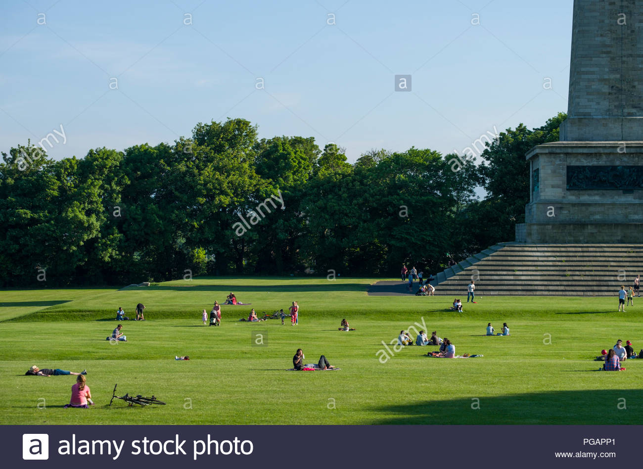Many people sitting in groups on the green lawn enjoying the afternoon sunshine at the Wellington Monument in Phoenix Park, Dublin, Leinster, Ireland Stock Photo