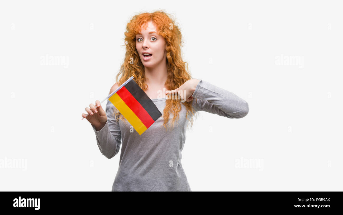 Young Redhead Woman Holding Flag Of Germany With Surprise Face Pointing Finger To Himself Stock