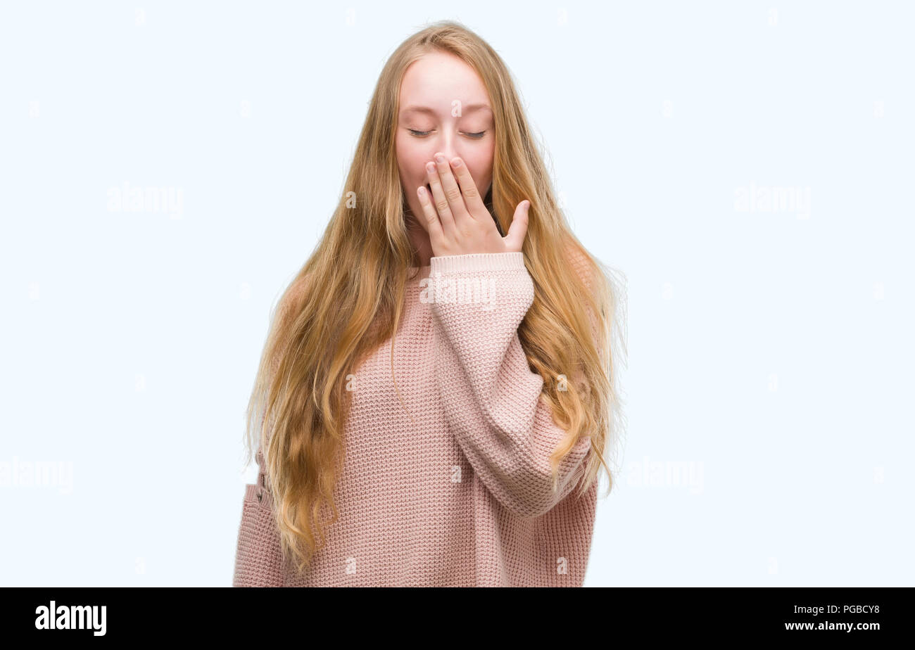 de8d1d119 Blonde teenager woman wearing pink sweater bored yawning tired covering  mouth with hand. Restless and