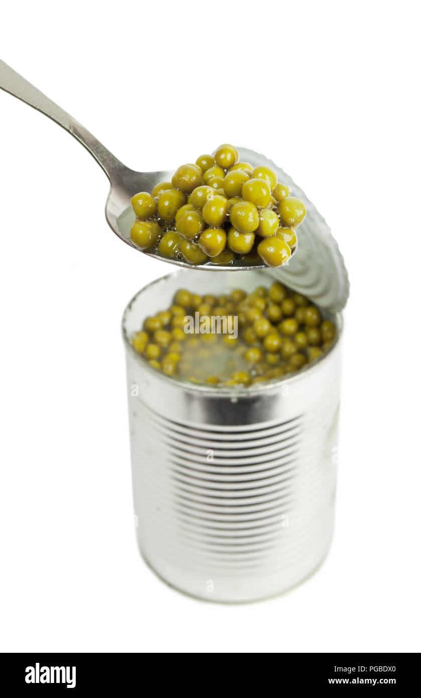 Preserved peas vegetable in metal spoon closeup isolated on a white background - Stock Image