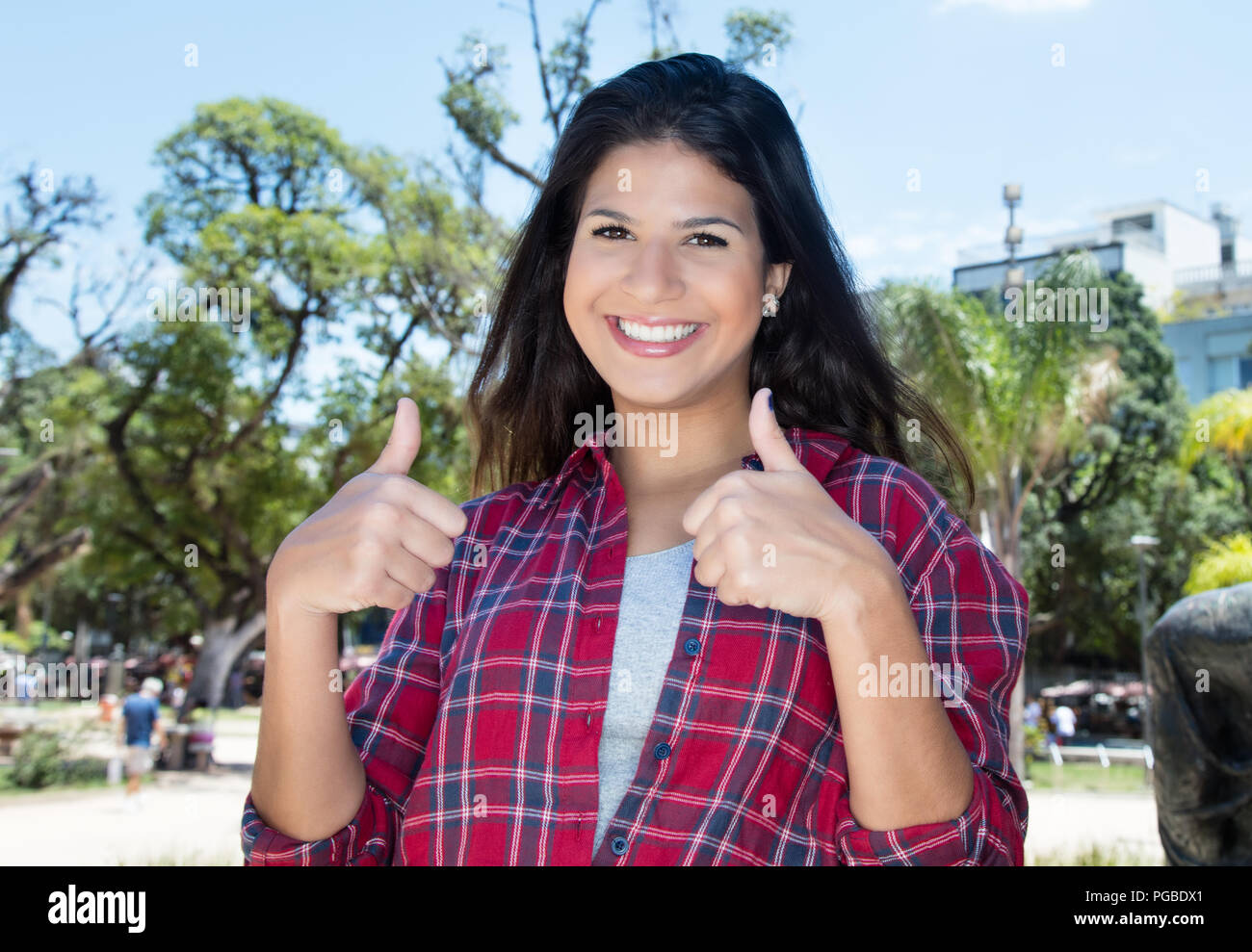 Caucasian woman with hipster shirt showing both thumbs outdoors in summer in city Stock Photo