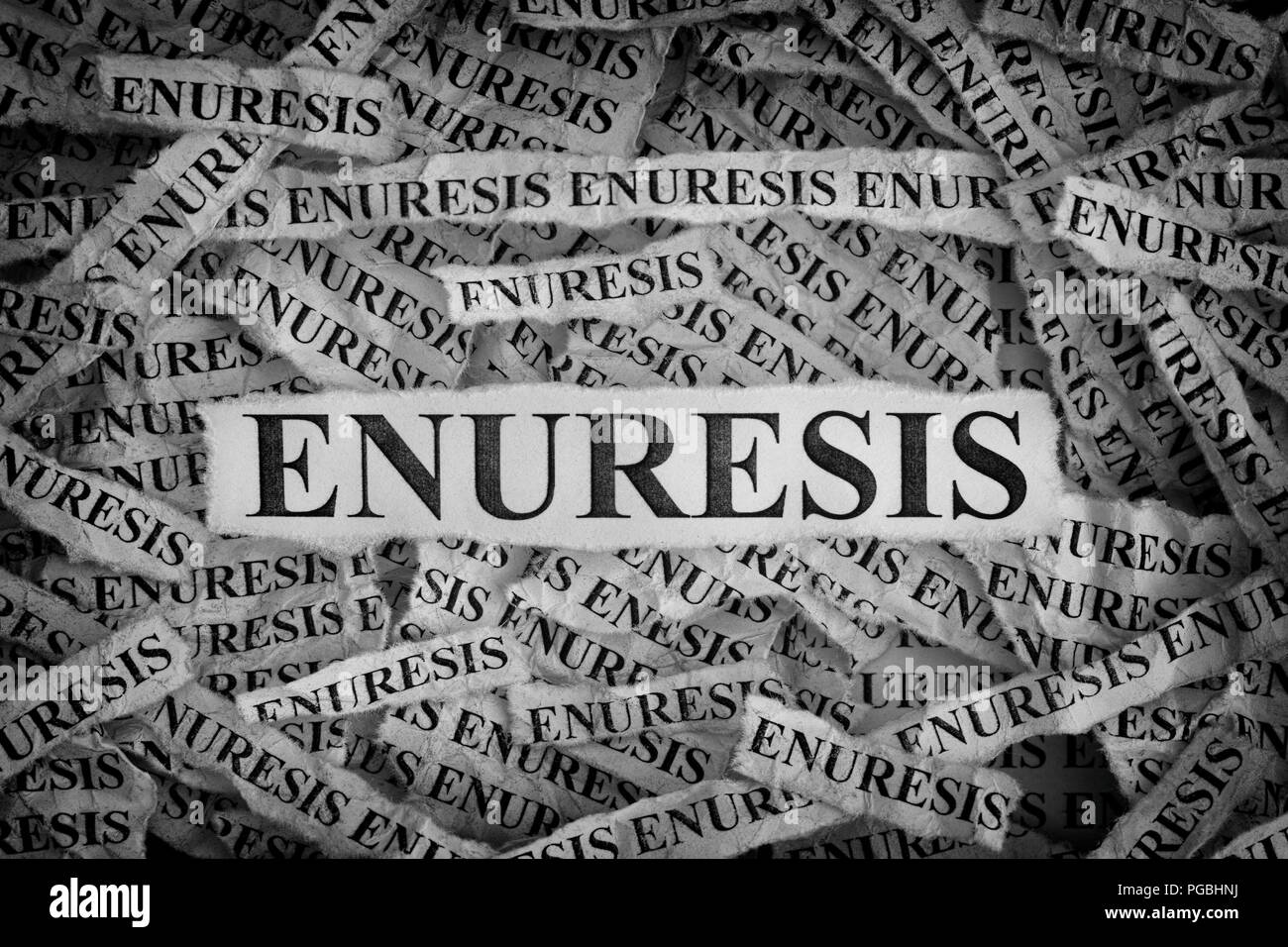 Enuresis. Torn pieces of paper with the words Enuresis. Concept Image. Black and White. Closeup. - Stock Image