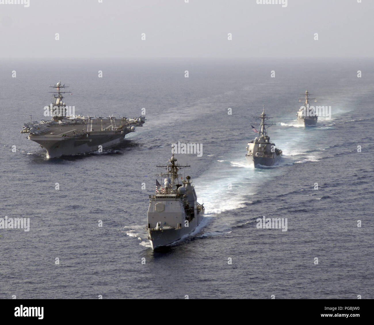 The US Navy (USN) Ticonderoga Class Guided Missile Crusier USS MOBILE BAY (CG 53) (front), Arleigh Burke Class Guided Missile Destroyers USS RUSSELL (DDG 59) and USS SHOUP (DDG 86) (right) perform a pass and review with the USN Nimitz Class Aircraft Carrier USS ABRAHAM LINCOLN (CVN 72) in the South China Sea. - Stock Image
