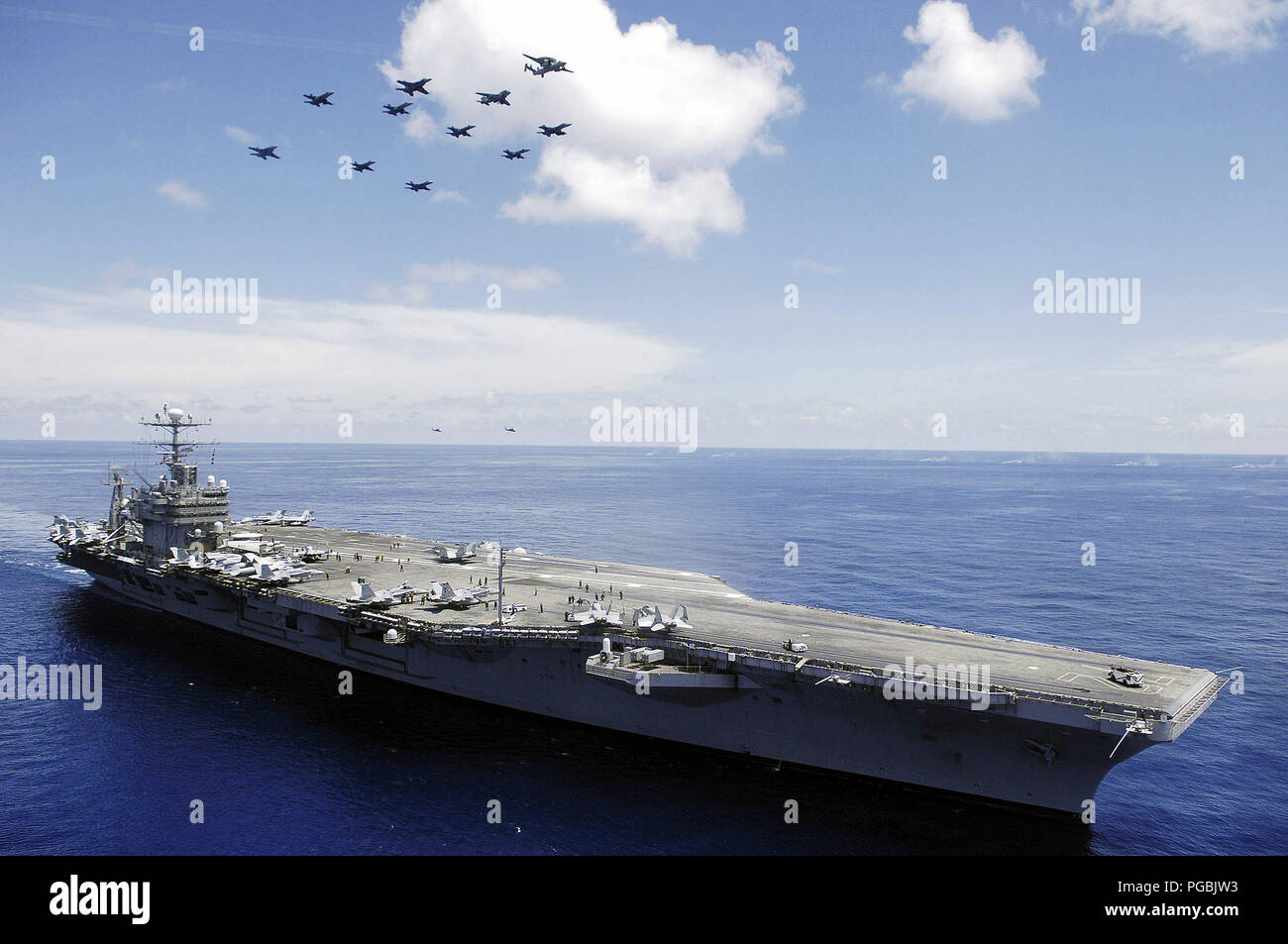 In the South China Sea, the US Navy (USN) Nimitz-class aircraft carrier USS ABRAHAM LINCOLN (CVN 72) and aircraft assigned to Carrier Air Wing Two (CVW-2) perform an aerial demonstration. - Stock Image