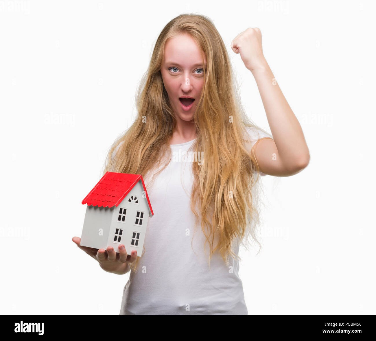 Blonde teenager woman holding family house annoyed and frustrated shouting with anger, crazy and yelling with raised hand, anger concept - Stock Image